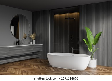 Corner of stylish bathroom with gray and wooden walls, wooden floor, comfortable bathtub, shower stall and sink with round mirror. 3d rendering