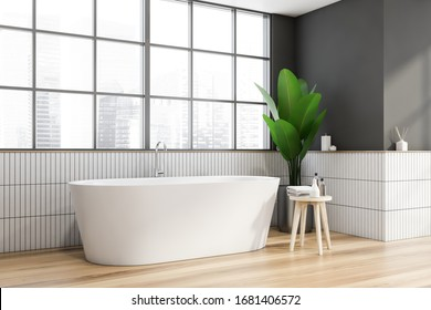 Corner of stylish bathroom with grey and white tiled walls, wooden floor, comfortable white bathtub standing under window with blurry cityscape and chair with beauty products. 3d rendering