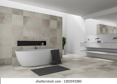 Corner of stylish bathroom with white and beige tile walls, white bathtub with gray towel hanging on it and double sink. 3d rendering