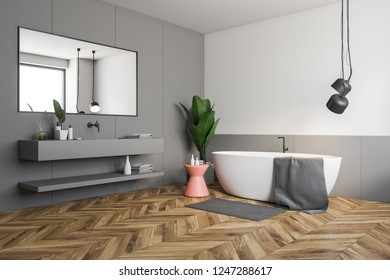 Corner of stylish bathroom with white and gray walls, wooden floor, white bathtub with pink chair near it and gray sink with horizontal mirror. 3d rendering