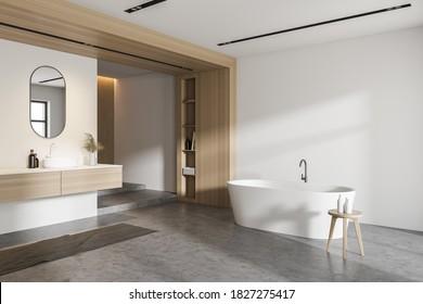 Esquina de un elegante cuarto de baño con paredes blancas y de madera, suelo de hormigón, cómoda bañera y lavabo con espejo. 3.ª representación
