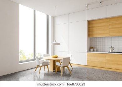 Corner of stylish kitchen with white tile walls, concrete floor, wooden countertops and cupboards, round dining table with white chairs and window with tropical view. 3d rendering