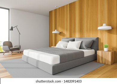 Corner of stylish master bedroom with white and wooden walls, wooden floor with gray carpet, comfortable king size bed and armchair with floor lamp. 3d rendering