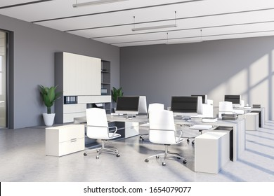 Corner of stylish open space office with grey walls, concrete floor, row of white computer tables with chairs and white bookcase with folders. 3d rendering
