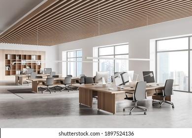Esquina de una elegante oficina abierta con paredes blancas y de madera, suelo de hormigón, fila de mesas de ordenador y biblioteca. 3.ª representación