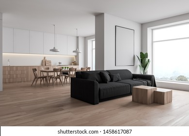 Corner of white living room with wooden floor, gray sofa, coffee table, vertical mock up poster frame and kitchen in background. 3d rendering