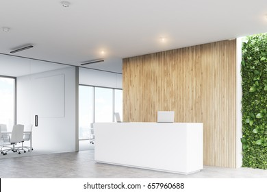 Corner of a white reception desk with two laptops standing on it in front of a wooden office wall. There is a grass wall seen through a wall opening. 3d rendering, mock up