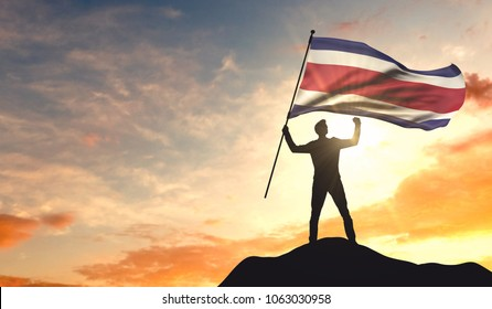 Costa Rica flag being waved by a man celebrating success at the top of a mountain. 3D Rendering