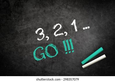 Counting down to Go concept with a handwritten countdown 1, 2, 3, and GO on a chalkboard in green and white letters with sticks of chalk