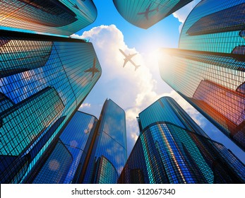 Creative abstract business corporate construction industry and real estate financial concept: blue modern high tall glass reflective skyscrapers in city downtown district with sun light and airliner