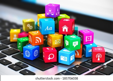 Creative abstract computer media and internet communication business concept: macro view of heap of colorful cubes with application icons and symbols on laptop keyboard with selective focus effect