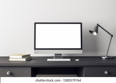 Creative designer desktop with empty computer and lamp on white concrete wall background. Mock up, 3D Rendering
