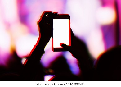 Creative double exposure illustration with concert fans filming event with smartphone camera.Fan takes pictures with mobile phone on festival in night club.Empty phones screen to place logo and text