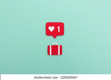 Creative paper cutout of like counter notification icon with suitcase on blue background