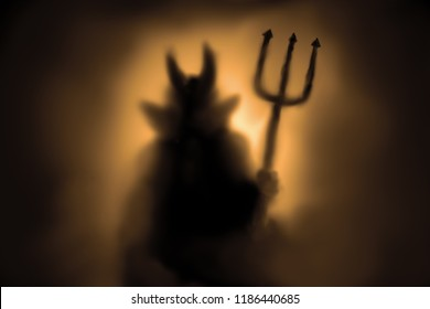 Creepy Devil silhouette behind a frozen glass and in the mist with backlit.