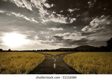 Crossroad in rural landscape under dusk sky