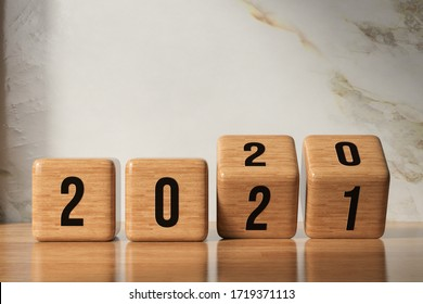 cubes turning from year 2020 to 2021 in front of marble background - 3D rendered illustration