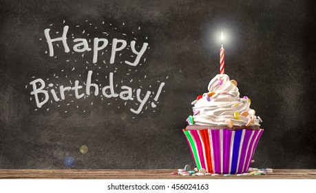 Cupcake with cream, candies and a candle on a wooden table with Happy Birthday written on a blackboard background. Empty free copy space available. 3D Rendering