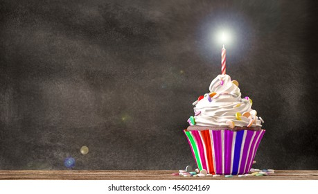 Cupcake with cream, candies and a candle on a wooden table with a blackboard background. Empty free copy space available. 3D Rendering