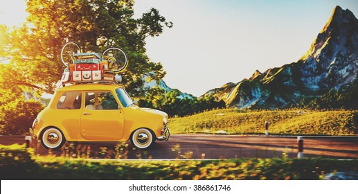 Cute little retro car with suitcases and bicycle on top goes by wonderful countryside road at sunset