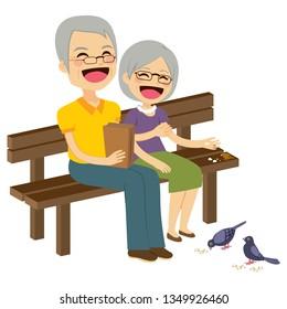Cute senior couple feeding birds with breadcrumbs sitting on bench