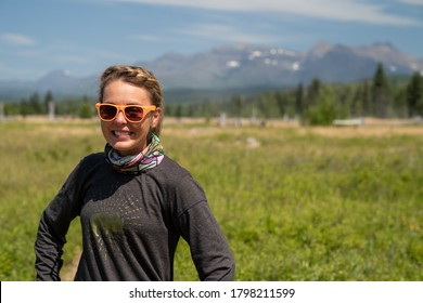 Cute, wholesome adult woman with braided hear poses in a meadow in Polebridge Montana. Neck gaiter (face mask) and smiling