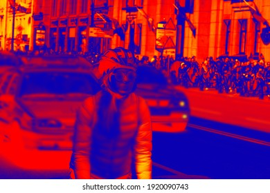 Cyclist girl on a crowded street with traffic. Scanning the people's body temperature with a thermal imager. Blurred anonymous people