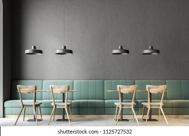 Dark gray wall cafe interior with a concrete floor, and wooden tables with chairs. Green sofas. 3d rendering mock up