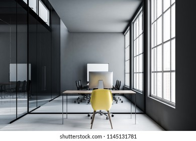 Dark gray walls office workplace with loft windows, a wooden table with a computer screen on it and a yellow chair. 3d rendering mock up