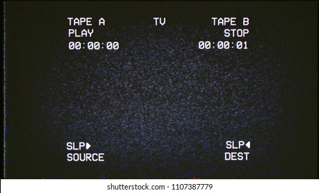 A dark tv screen in the shadows, showing noise from an old VHS tape tracking a bad signal. Double deck layout. Retro vintage background.
