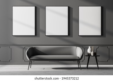 Dark waiting room interior with comfortable couch, small coffee table and three empty white poster on the grey wall. Concrete floor. Scandinavian minimalist style design. Mock up. 3d rendering