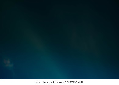 Defocused teal blue glow. Dark abstract art background. Colored lens flare light leak.