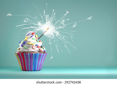 Delicious cupcake with a glittering sparkler and smarties on a whipped cream. Copy space available.