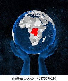 Democratic Republic of Congo on translucent blue globe held in hands in space. 3D illustration.