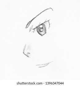 detail of female anime face with eye and nose hand-drawn by black pencil on white paper