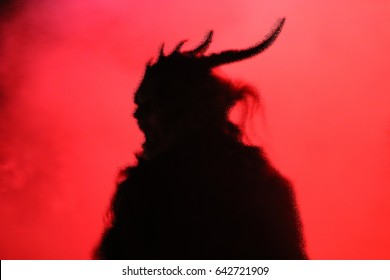 devil in horror scream pose with artistic dispersion silhouette effect with red background