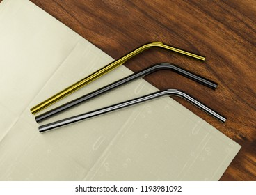 Different color stainless metal drinking straw on a wooden table 3D rendering 3D illustration