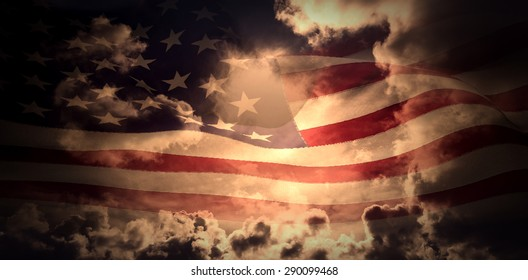 Digitally generated american flag rippling against dark sky with white clouds