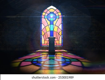 A dim old church interior lit by suns rays penetrating through a colorful stained glass window in the pattern of a crucifix reflecting colors on the floor and a speech pulpit