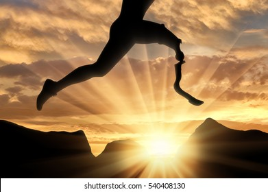 Disabled athlete with prosthetic leg jumping over stones on background sunset. Concept disability and sport