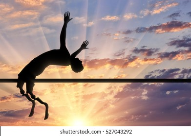 Disabled jumps with artificial limb jumps over crossbar up sunset. Concept handicapped and sport