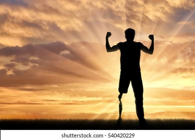 Disabled person with prosthetic leg standing on hill and raise hands up on sunset. Concept disabled