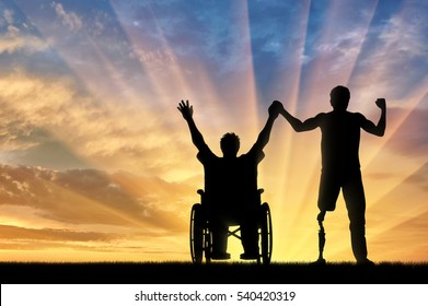 Disabled person with prosthetic leg and disabled in wheelchair holding hands on sunset. Concept disabled