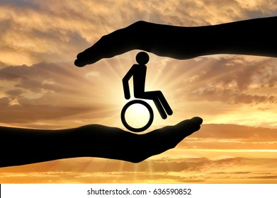 Disabled person in a wheelchair in hands. Concept of helping people with disabilities