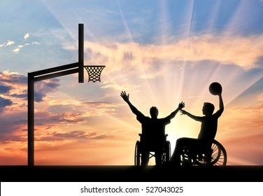Disabled sportsman in wheelchair play basketball on basketball court with ball sunset. Concept sport and willpower