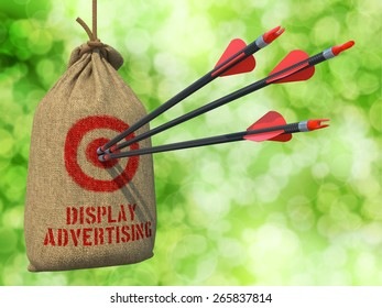 Display Advertising - Three Arrows Hit in Red Target on a Hanging Sack on Natural Bokeh Background.