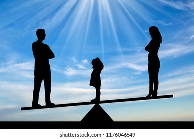 Divorce in the family. Silhouette of a little sad girl crying standing between mom and dad, chooses to stay with dad. The concept of divorce and division of children