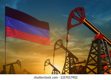 Donetsk Peoples Republic oil industry concept, industrial illustration. Fluttering Donetsk Peoples Republic flag and oil wells on the blue and yellow sunset sky background - 3D illustration