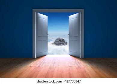 Door opening in dark room to show sky against mountain peak through the clouds