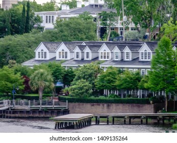 Dormers on townhomes above green trees and waterfront docks along the Cape Fear River in Wilmington, North Carolina, USA, with digital oil-painting effect, for residential, urban, or coastal themes